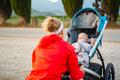 Mother with stroller enjoying motherhood at sunset landscape