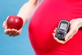 Pregnant woman with apple and glucose meter with good result sugar level