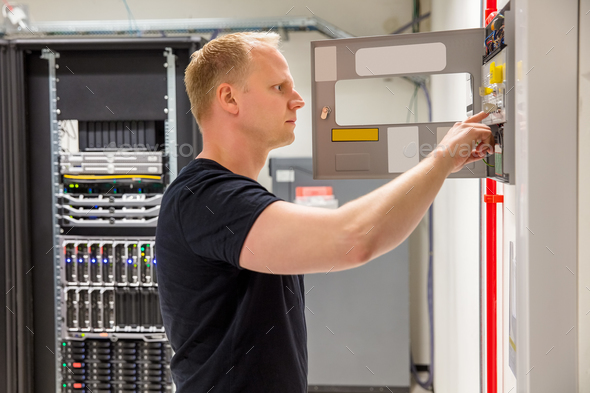 Confident Male Technician Checking Fire Panel In Datacenter - Stock Photo - Images