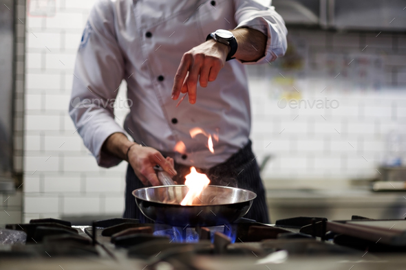 A man cooks cooking deep fryers in a kitchen fire. - Stock Photo - Images