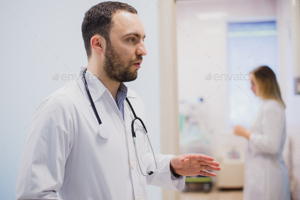 pensive young doctor in white coat holding diagnosis in hospital, caring doctor concept - Stock Photo - Images