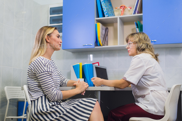 female doctor talking with patient in doctors office - Stock Photo - Images