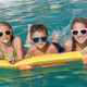 Three happy children playing on the swimming pool at the day tim - PhotoDune Item for Sale