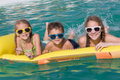 Three happy children playing on the swimming pool at the day tim