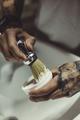 Crop tattooed barber making foam