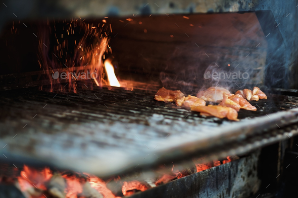 cooking pieces of raw meat in a brazier on an open fire - Stock Photo - Images
