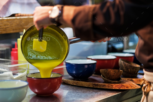 Man cooking tasty orange soup or sauce - Stock Photo - Images