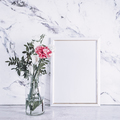 Blank frame and pink flowers over marble table - PhotoDune Item for Sale