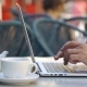 Man Types Something on His Laptop Sitting at the Table in Cafe - VideoHive Item for Sale