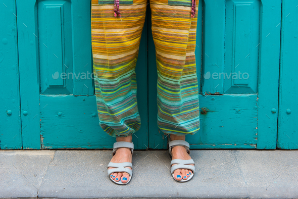 Feet of a woman in sandals with blue toe nails. Colorful hippie pants. Detail - Stock Photo - Images