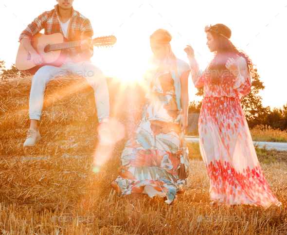 Hippie friends with guitar in a wheat field - Stock Photo - Images