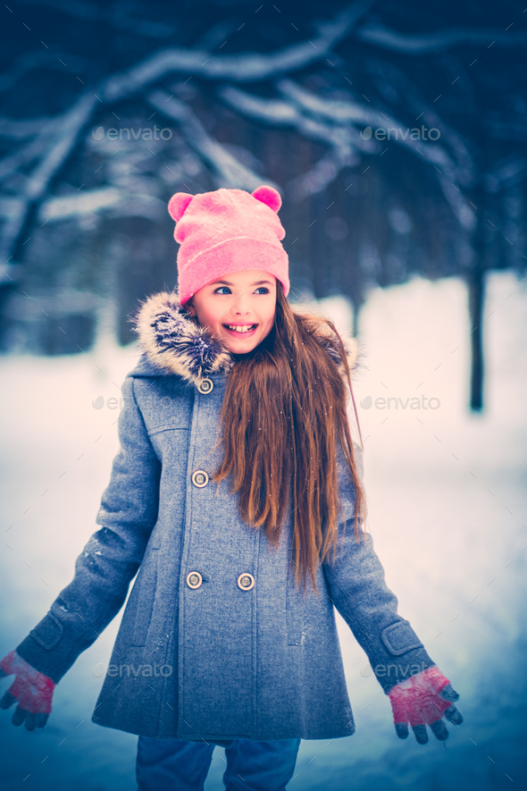 Charming little girl in a snow - Stock Photo - Images