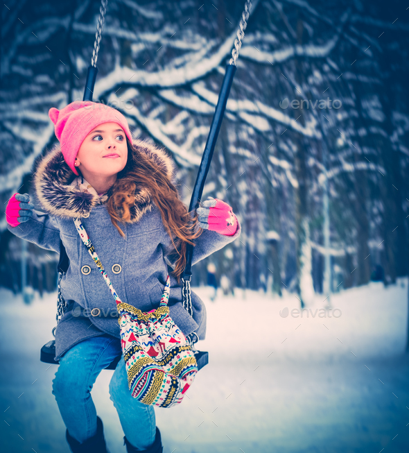 Charming little girl on swing in snowy winter - Stock Photo - Images