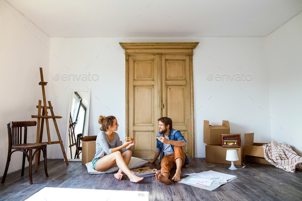 Young couple moving in new house, eating pizza. - Stock Photo - Images