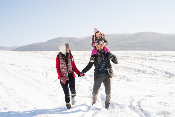 Father and mother with their daughter on a walk, winter nature. - Stock Photo - Images