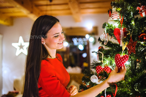 Young woman in front of Christmas tree decorating it - Stock Photo - Images