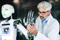 Mature businessman or scientist with a robot. - PhotoDune Item for Sale