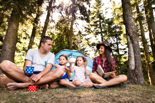 Beautiful young family with daughters camping in forest. - Stock Photo - Images