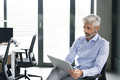 Mature businessman with tablet in the office. - PhotoDune Item for Sale