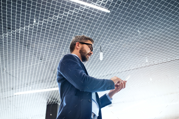 Hipster businessman in the office with smartphone. - Stock Photo - Images
