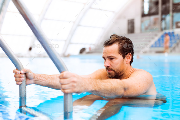 Man getting out of the indoor swimming pool. - Stock Photo - Images
