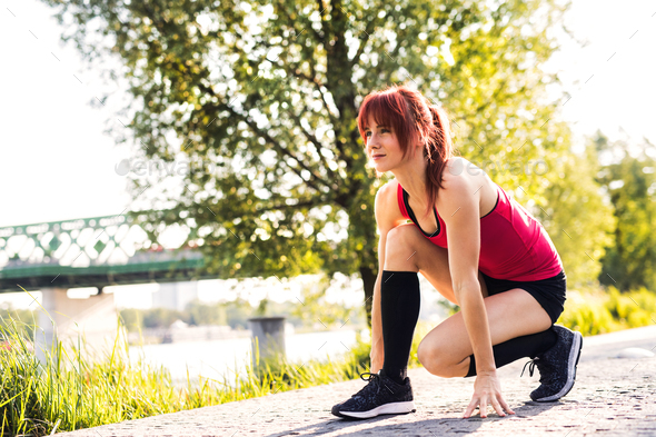 Beautiful young runner on a path in the city park. - Stock Photo - Images
