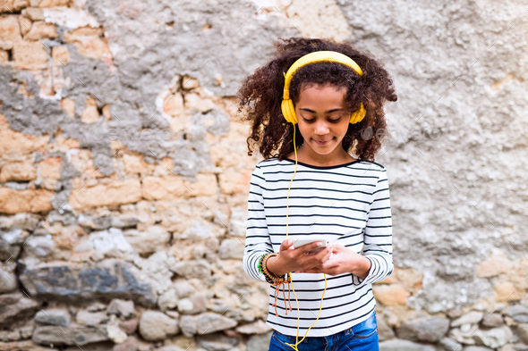 Beautiful african american girl with smart phone and earphones. - Stock Photo - Images