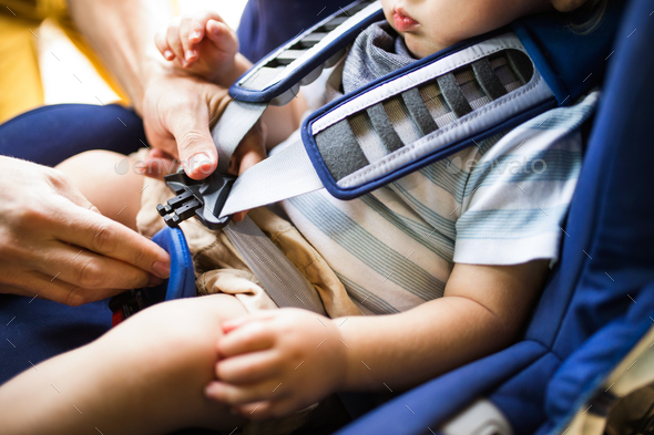 Father fastening seat belt for his son sitting in the car. - Stock Photo - Images