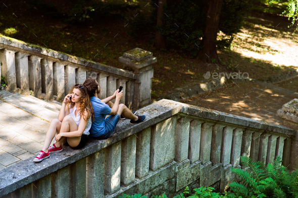 Young couple with smartphones in town sitting on concrete wall. - Stock Photo - Images