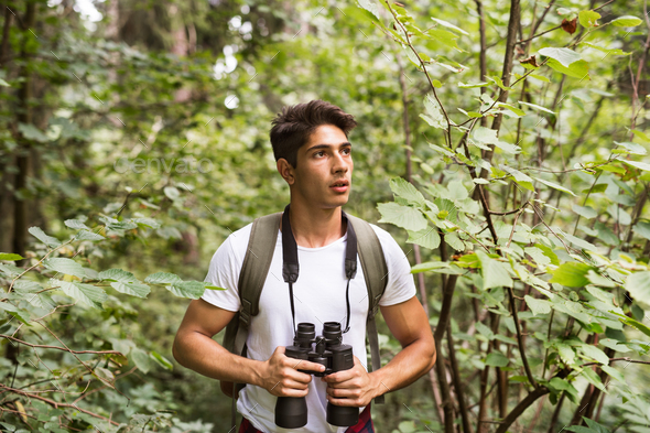 Teenage boy with binoculars hiking in forest. Summer vacation. - Stock Photo - Images