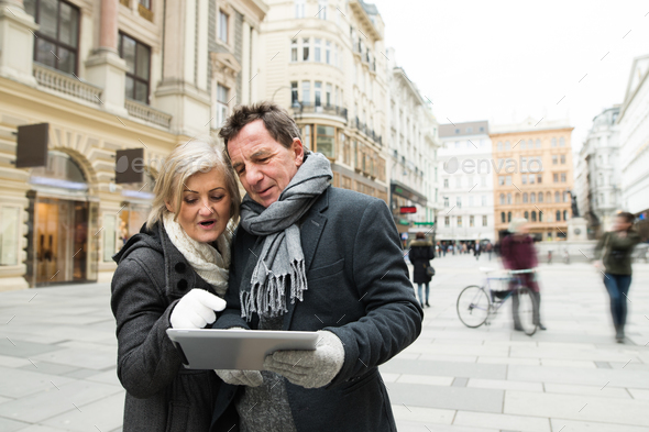 Beautiful senior couple with tablet on a walk in city centre. - Stock Photo - Images