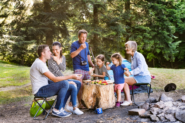 Beautiful family camping in forest, eating together. - Stock Photo - Images