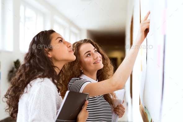 Two teenage girls in high school hall during break. - Stock Photo - Images
