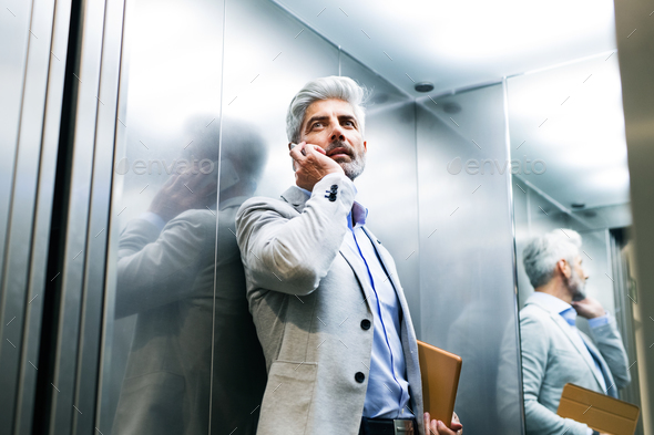 Mature businessman with smartphone in the elevator. - Stock Photo - Images