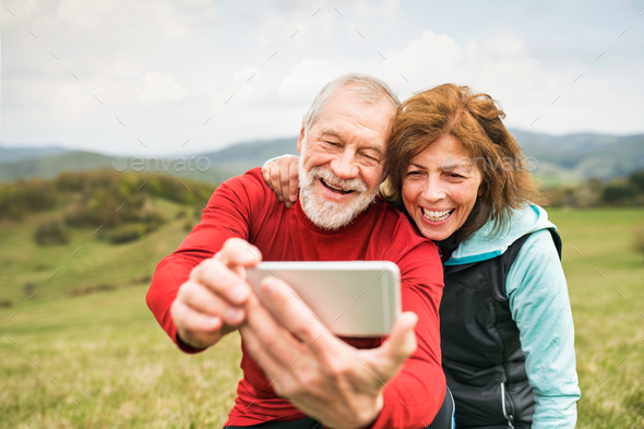 Active senior runners in nature taking photo with smart phone. - Stock Photo - Images