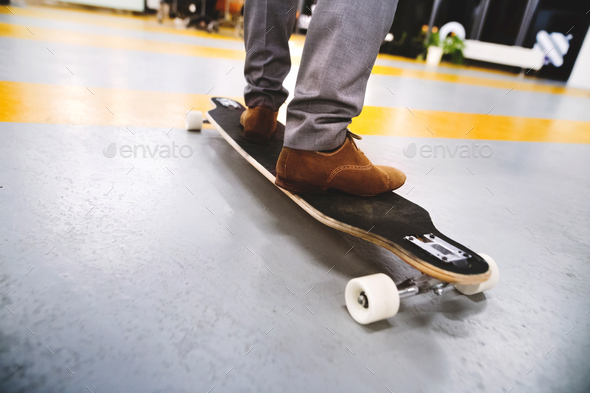 Unrecognizable businessman standing on longboard. - Stock Photo - Images