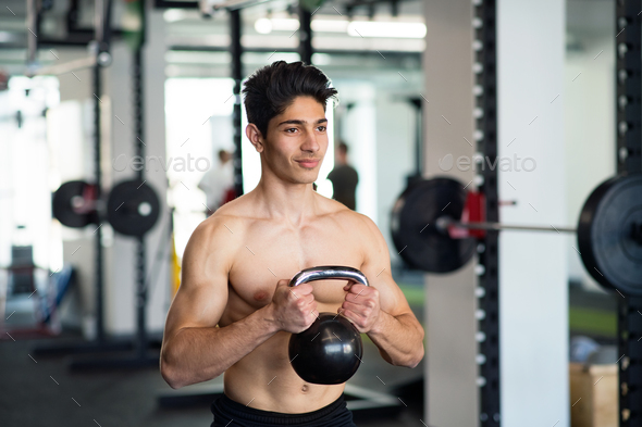 Young fit hispanic man in gym exercising with kettlebell. - Stock Photo - Images