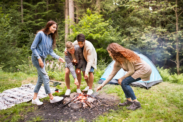 Beautiful teenagers in forest at bonfire with sparklers. - Stock Photo - Images