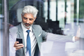 Mature businessman with smartphone in the office. - PhotoDune Item for Sale