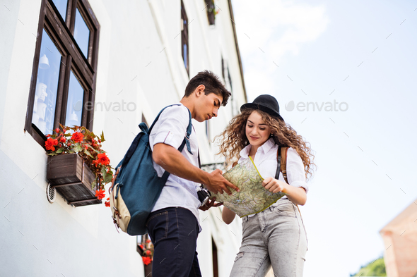 Two young tourists with map and camera in the old town - Stock Photo - Images