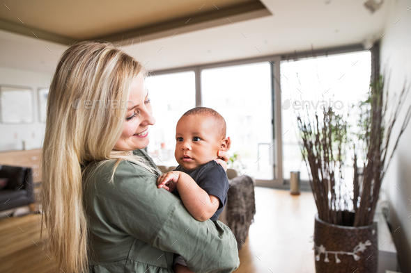 Beautiful young mother with her little baby boy at home. - Stock Photo - Images