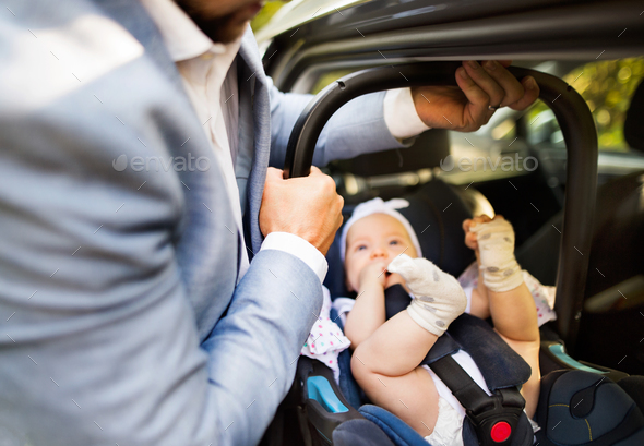 Unrecognizable man putting baby girl in the car. - Stock Photo - Images