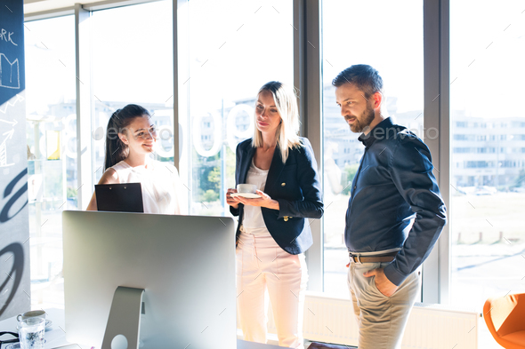 Three business people in the office working together. - Stock Photo - Images
