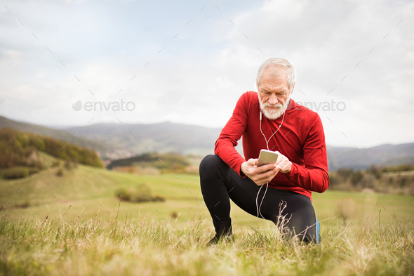 Active senior runner in nature with smart phone and earphones. - Stock Photo - Images