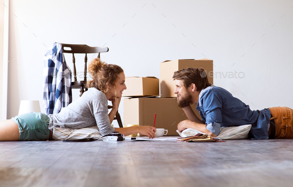 Young couple moving in new house, lying on the floor. - Stock Photo - Images