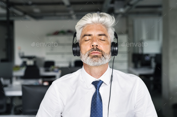 Mature businessman with headphones in the office. - Stock Photo - Images
