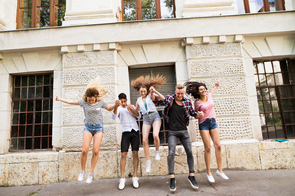 Group of teenage students in front of university jumping high. - Stock Photo - Images