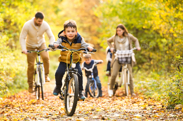 Young family in warm clothes cycling in autumn park - Stock Photo - Images