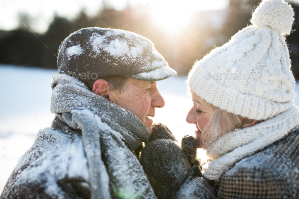 Beautiful senior couple on a walk in sunny winter nature - Stock Photo - Images