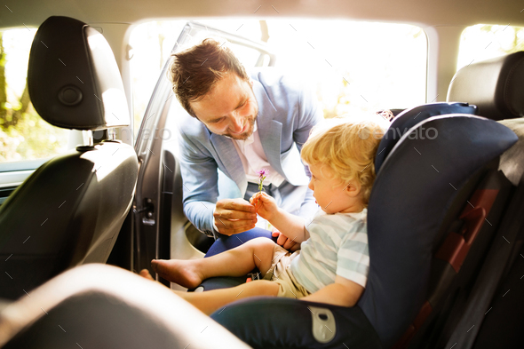 Father putting his son in the car. - Stock Photo - Images